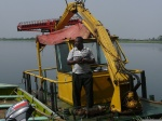 Tetteh Okantey, chief operator of the weed harvester, posing with his baby