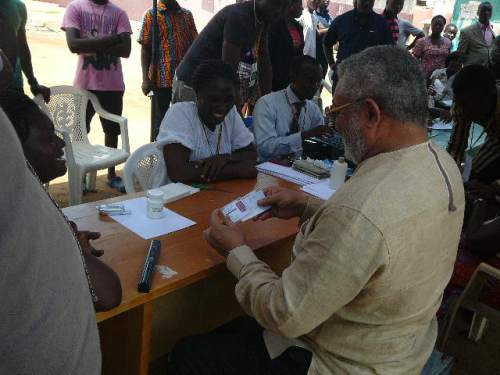 President Rawlings inspects his biometric voter identity card