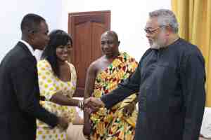 President Rawlings in a handshake with Grace Ashe, Nkosuohemaa of Suma Ahenkro